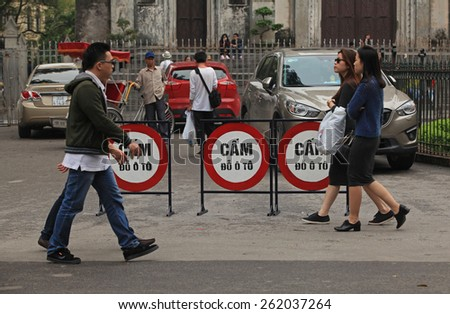 Hanoi, Vietnam - Mar 15, 2015: Daily street life in Vietnam. People walking on a street of Hanoi capital with no parking sign.  - stock photo