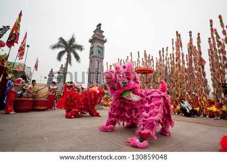 HANOI, VIETNAM - MARCH 29: A group of unidentified boys dance with their colorful lion during the Tet Lunar New Year celebrations on March 29, 2012 in Ha Noi City, Vietnam. - stock photo