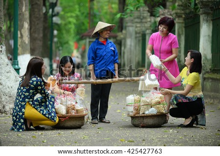 Hanoi, Vietnam, May 16, 2016: Early morning in a street in Hanoi's Old Quarter ( Pho co Hanoi). Vietnam girls wear Ao dai (long dress) and street vendors on the ancient city of Hanoi.