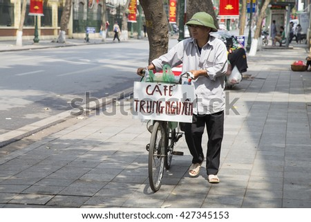 Hanoi, Vietnam - May 21, 2016: Vietnamese vendor selling coffee beverage drink with a mobile tall on a bicycle on sidewalk of a street in Hanoi capital.
