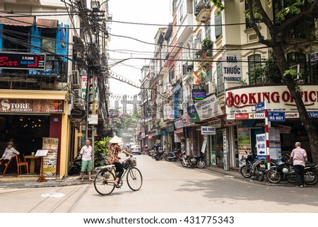 Hanoi, Vietnam - May 18, 2016: Woman wearing the traditional Vietnamese hat cycling in a street of Hanoi's Old Quarter.