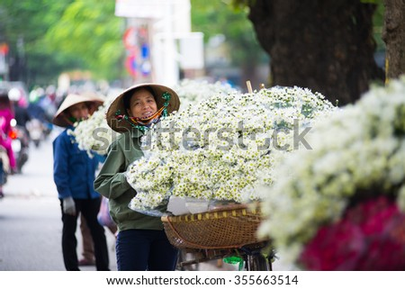 HANOI, VIETNAM - NOVEMBER 25: White daisy flower vendor in a street in Hanoi on November 25, 2015 in Hanoi, Vietnam. In Vietnam white daisy flowers bloom in November.