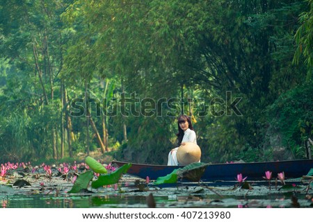 "HANOI, VIETNAM - OCT 18: Girl with ""AO DAI"" on traditional boat in water lily river visit Huong pagoda in Hanoi, Vietnam on October 18, 2015. Huong pagoda in hanoi have beauty landscape for traveler."