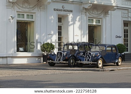 HANOI, VIETNAM - OCT 8, 2014: Two old Citroen cars parking in front of Hotel Sofitel Legend Metropole Hanoi. These cars are for rent for tours around old street of Hanoi. - stock photo