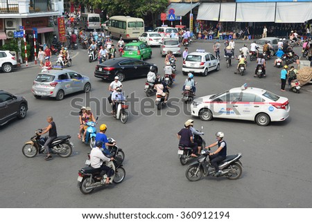 Hanoi , VIETNAM - October 25, 2015: A lot of motorcyclists and vehicles drive at the road crossing. - stock photo