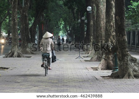 HANOI, VIETNAM - OCTOBER 14, 2015 : Local Vietnamese taking a ride along the lush stretch of road at Phan Dinh Phing road in Hanoi, Vietnam.