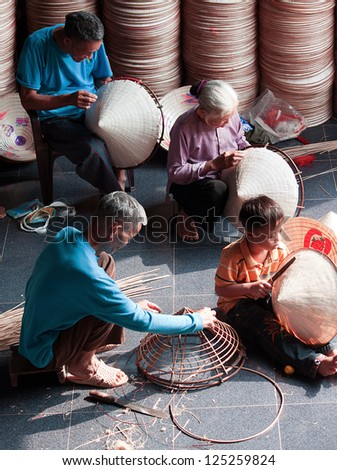 HANOI, VIETNAM - OCTOBER 23: unidentified vietnamese a family sitting sewing hats in a traditional village in Vietnam October 23, 2010. Conical hat is an traditional item of ethnic Vietnam - stock photo