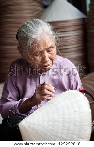 HANOI, VIETNAM - OCTOBER 23: Vietnamese woman sitting sewing hats in a traditional village in Vietnam October 23, 2010. Conical hat is an traditional item of ethnic Vietnam - stock photo