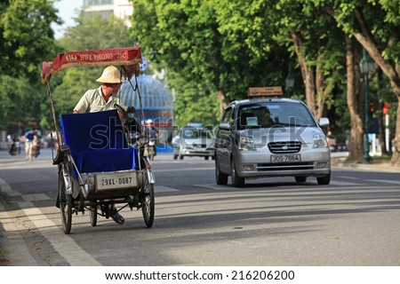 HANOI, VIETNAM - SEP 7, 2014: Popular type of transportation for foreign visitors in Vietnam, cyclo rickshaw and taxi, on Hanoi street,