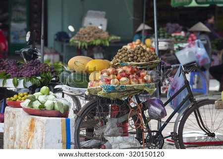 Hanoi, Vietnam - Sep 19, 2015: Typical scene of life in Vietnam as well as South East Asia with many kinds of tropical fruits displayed on vendor's bicycle at a flea market in Hanoi capital.