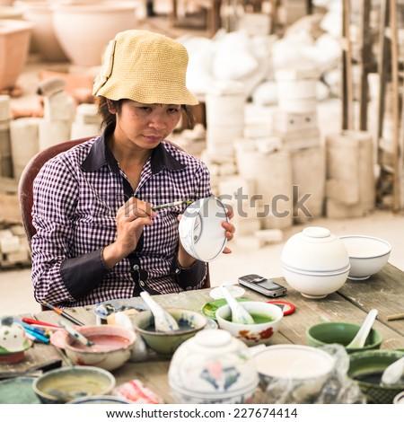 HANOI, VIETNAM - SEP 24, 2014: Unidentified Vietnamese woman draws on the ceramic dish in the ceramic workshop. Ceramic art is very popular in Asian culture - stock photo