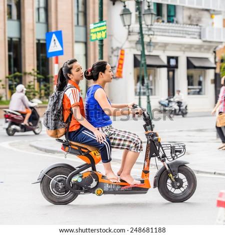 HANOI, VIETNAM - SEP 23, 2014: Unidentified Vietnamese women on motorbike. 92% of Vietnamese people belong to the Viet ethnic group - stock photo