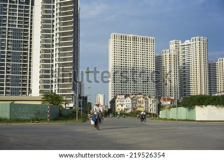 Hanoi, Vietnam - Sept 21, 2014: Unidentified woman cycling on outskirts street of Hanoi city, with high buildings on background