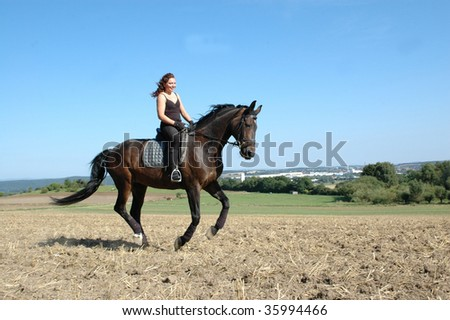 Hanoverian. Equestrienne gallops on field.