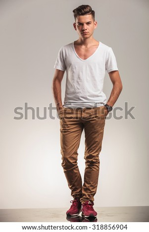 hansome young fashion men standing on studio backgroung with his hands in pockets - stock photo