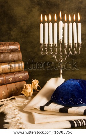 Hanukkah candleholder and jewish prayer shawl, books and cap - stock photo