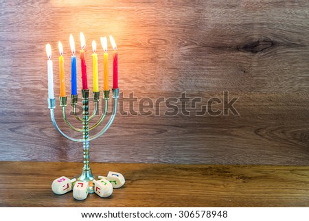 Hanukkah menorah with burning candles and wooden dreidels. - stock photo