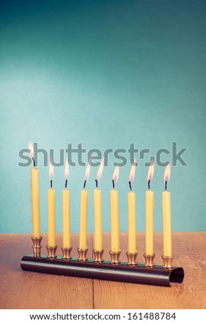 Hanukkah menorah with burning candles on table - stock photo