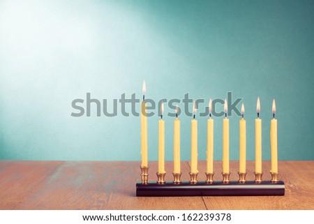 Hanukkah menorah with burning candles on table - stock photo