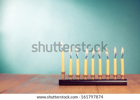 Hanukkah menorah with burning candles on wooden table - stock photo