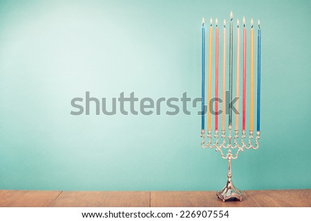 Hanukkah menorah with burning color candles for holiday card background - stock photo