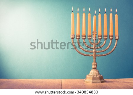 Hanukkah menorah with burning color candles for holiday card background. Retro old style filtered photo