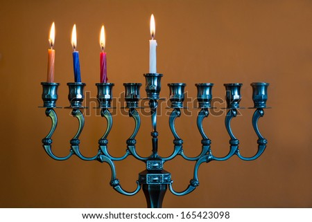 Hanukkah menorah with four burning candles on the third day of Hanukkah. - stock photo
