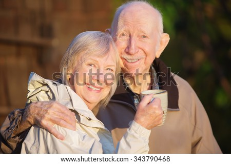 Happily married senior couple outdoors with coffee outdoors - stock photo