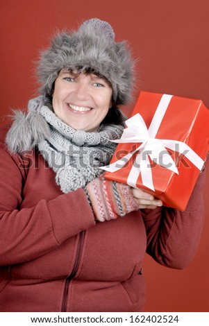 Happily smiling woman with a christmas present over red background - stock photo