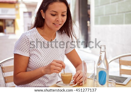 Happily thoughtful brunette stirring her coffee in a coffee shop smiling while wearing her hair loose and casual clothing