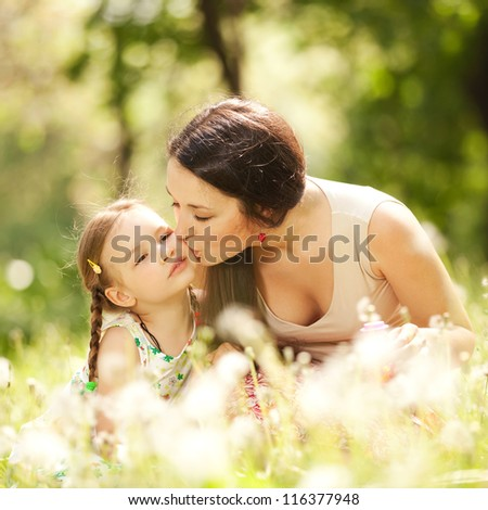 Happiness and harmony in family life. Happy family concept. Young mother kissing her daughter in the park. Happy family resting together on the green grass. Family having fun outdoor