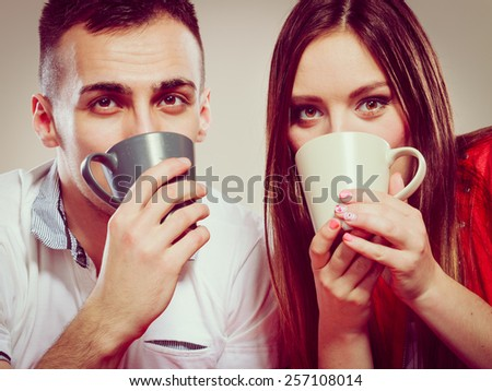 Happiness and healthy relationship concept. Attractive couple drinking tea or coffee together, closeup man and woman holding mugs with hot beverage - stock photo