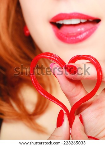 Happiness and love concept. Happy redhair woman smiling girl holding valentine red heart on pink. Valentines day.