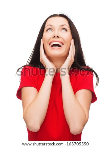 happiness and people concept - amazed laughing young woman in red dress - stock photo