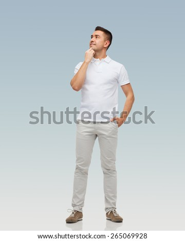 happiness and people concept - smiling man with hands in pockets looking up over gray background - stock photo