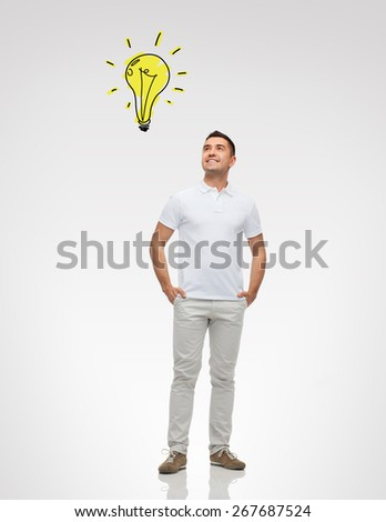 happiness and people concept - smiling man with hands in pockets looking up to lighting bulb doodle over gray background - stock photo