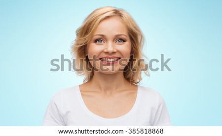 happiness and people concept - smiling woman in blank white t-shirt over blue background - stock photo