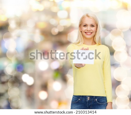 happiness and people concept - smiling young woman in casual clothes with white blank business or name card - stock photo