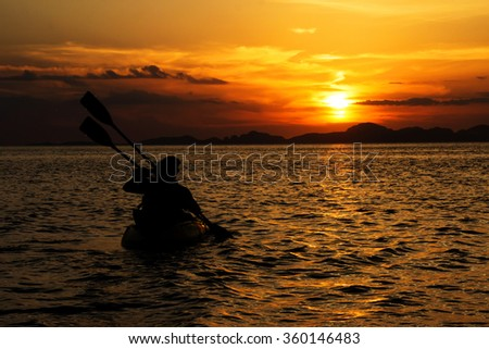 Happiness and romantic scene of love couples partners canoeing. Silhouette on sunset.