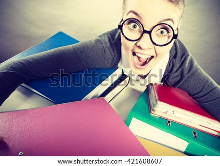 Happiness and satisfaction from working. Young positive happy blonde accountant at work. Crazy lovely woman surrounded of piles of colorful binders.