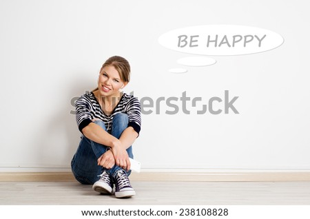Happiness and youth concept. Cheerful teenage girl dreaming listening music with drawn thought bubble on empty wall.  - stock photo