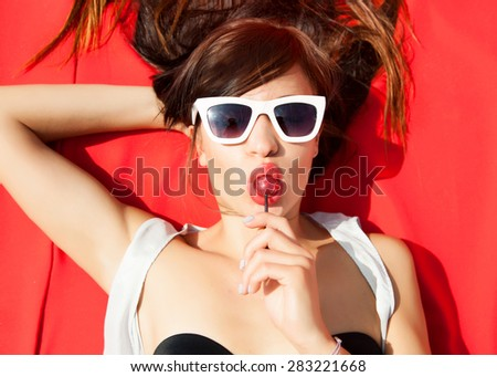 Happiness bliss freedom concept of sensual woman laying on red with summer sunglasses,eating sweets on bikini with glowing skin,having sunbath at hot sunny day.Summer outfit,fashion store,summer store - stock photo