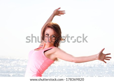 Happiness bliss freedom concept. Woman happy smiling joyful with arms up dancing on beach in summer during holidays travel. Beautiful young cheerful Caucasian female model - stock photo