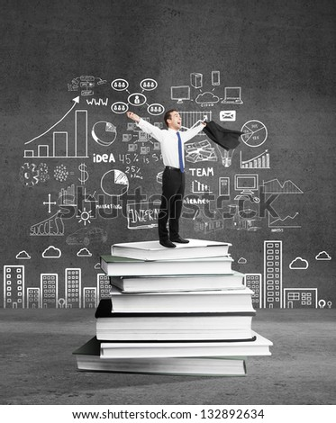 happiness businessman standing on books and drawing business concept - stock photo