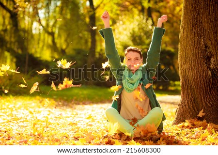 Happiness carefree. woman relaxing in autumn park throwing leaves up in the air with arms raised up. Beautiful girl in colorful forest foliage outdoor. - stock photo