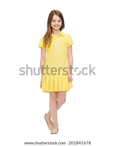 happiness, childhood and people concept - smiling little girl in yellow dress - stock photo