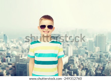 happiness, childhood, dreams and people concept - smiling little boy over green blue cloudy sky background - stock photo