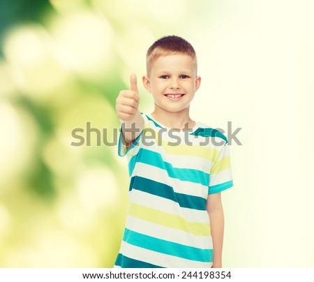 happiness, childhood, ecology and people concept - smiling little boy in casual clothes showing thumbs up over green background - stock photo