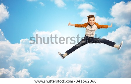 happiness, childhood, freedom, movement and people concept - happy smiling boy jumping in air over blue sky and clouds background - stock photo