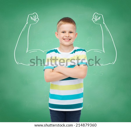 happiness, childhood, school, education and people concept - smiling little boy in casual clothes over green board background strong arms drawing - stock photo
